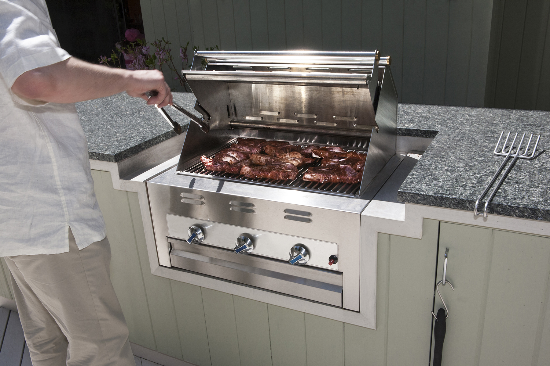 modern outdoor propane gas grill with man turning stakes