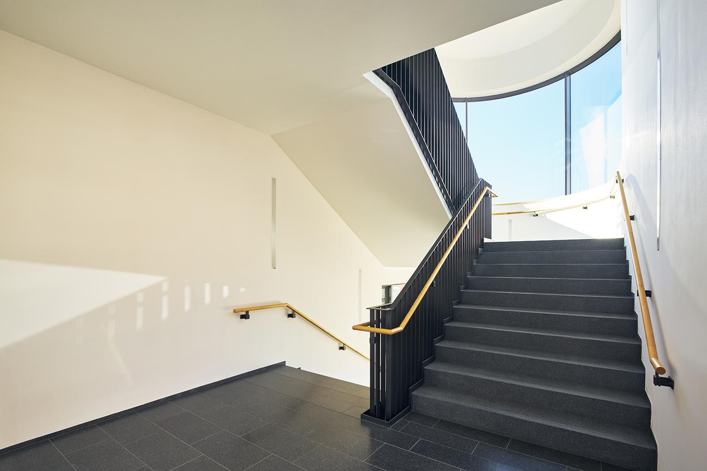 Treppe in Treppenhaus mit großen Fenstern mit Sonne und blauem Himmel
