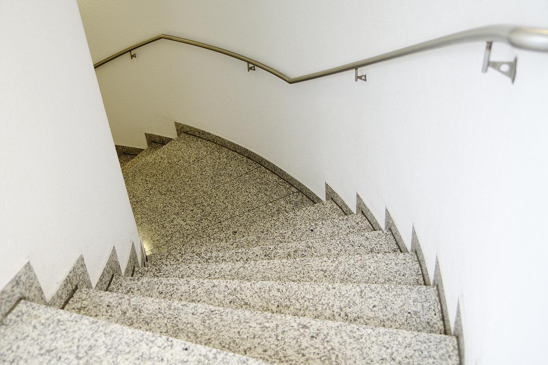 Modernes Treppenhaus mit Wendeltreppe aus Natursteinplatten